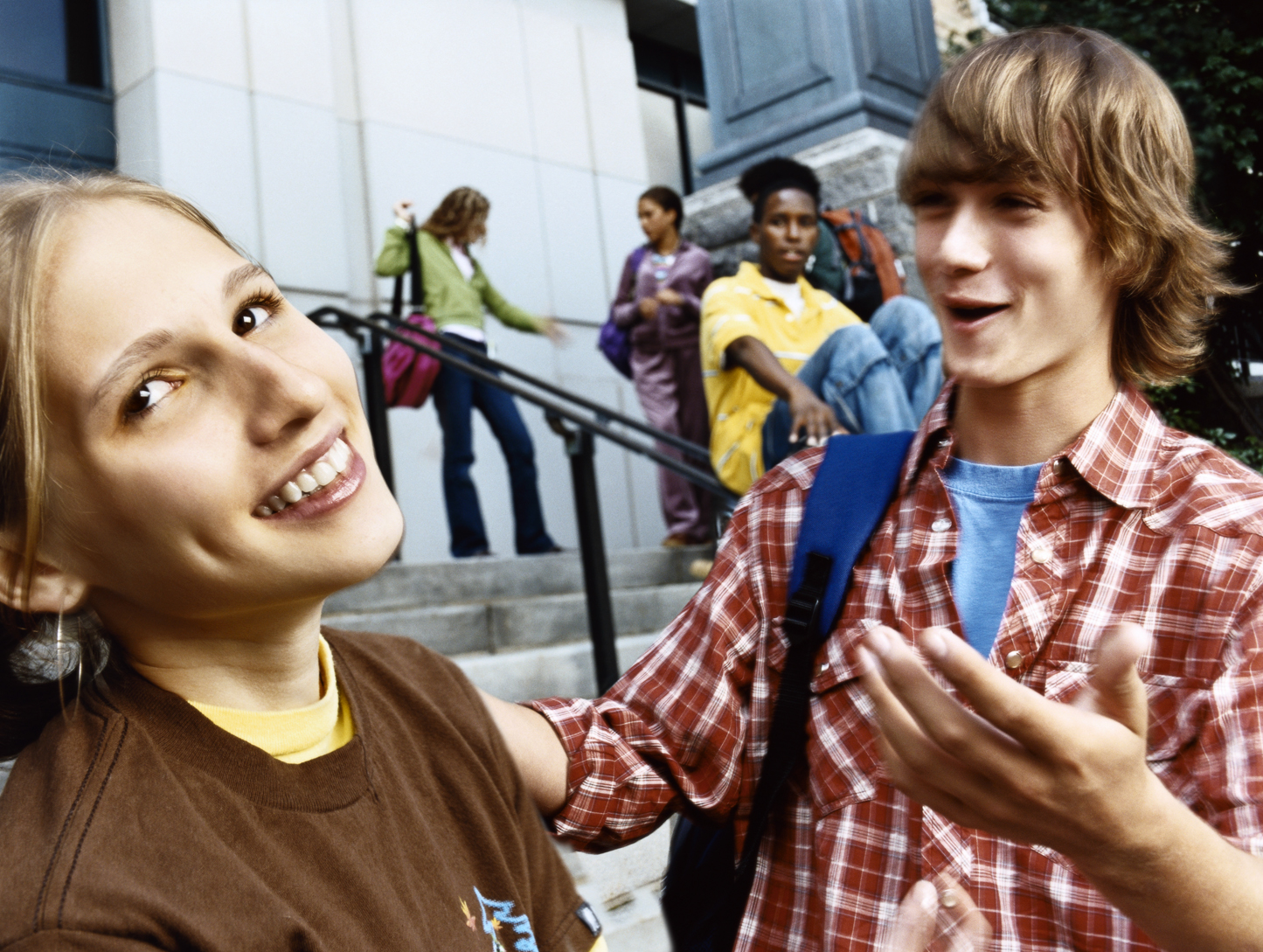 girl and boy laughing in front of school