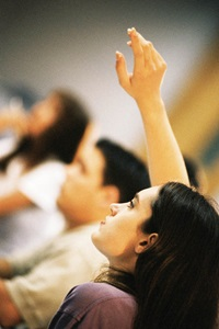 students in class, girl with her hand raised