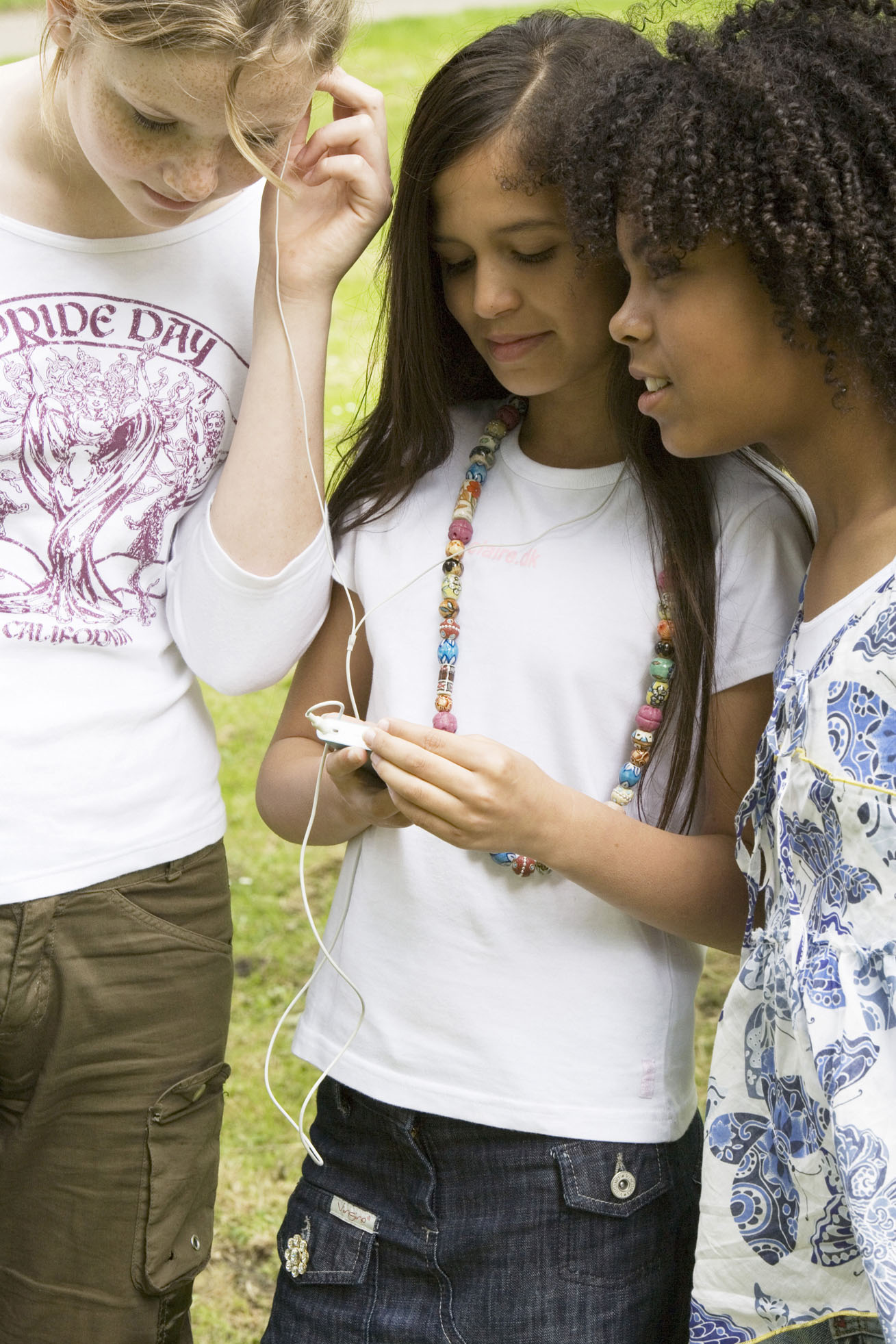 three girls looking at an ipod music player